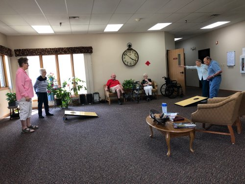 Mary, Mabel, Aletha, and Les playing bean bag toss while George and Bertha cheer them on!