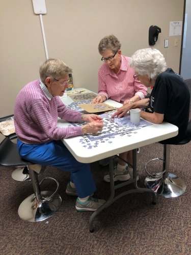 Aletha, Mary, and Mae working on the puzzle! We love to puzzle and always have one going!