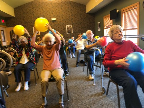 Residents enjoy doing arm exercises with the exercise balls