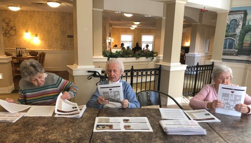 I'm not sure if these ladies are folding the newsletters or reading them?