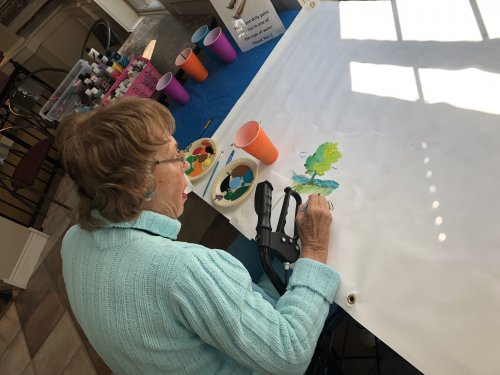 Artist Marian putting her inspiration on our Primrose Mural