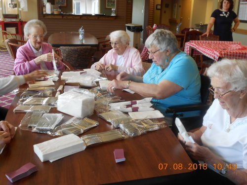 The Ladies working hard wrapping Silverware for our big Event on August 16th