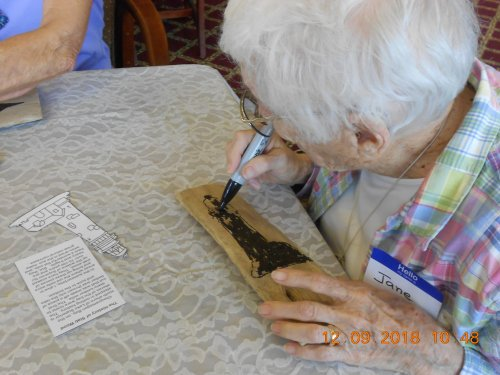 Jane working on her Lighthouse Slab Wood Painting.
