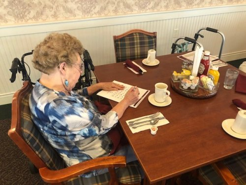 Ellie working on the August puzzle in the newsletter before Lunch starts