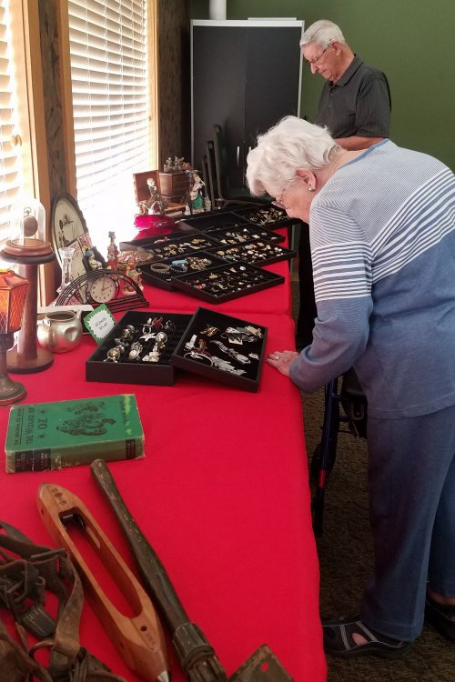 Joan M. and Don L. check out the antiques at the Vintage Pickers Estate sale display in the Wellness Center.
