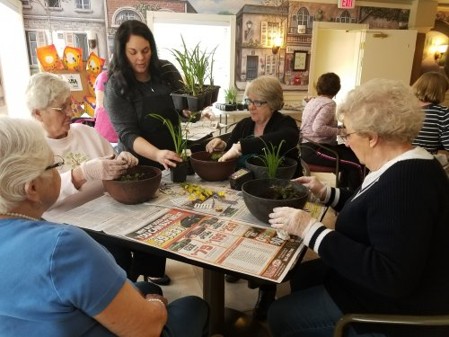 Susan hands out supplies for the miniature gardens