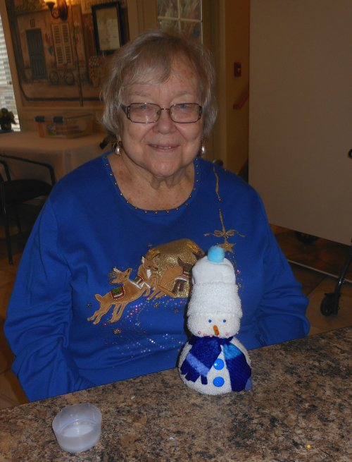 Barb and her snowman have matching attire.