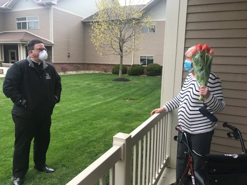 Father Scott stopped by to deliver prayers and flowers to one of his parishioners.