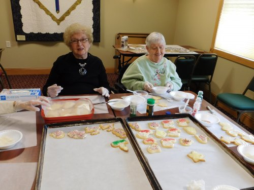 Residents, Darlene and Pat help with the Christmas cookie decorating project.