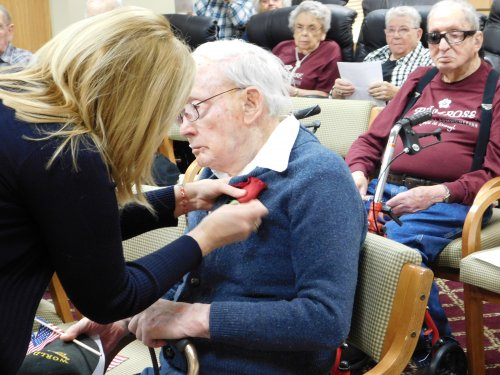 Executive Director Tonya pins a rose on WWII Veteran, Bud, at Grand Island's Veterans' Program.