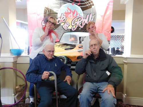 Residents Pat and Harold share a time with staff at our 50's Party, complete with candy cigarettes.