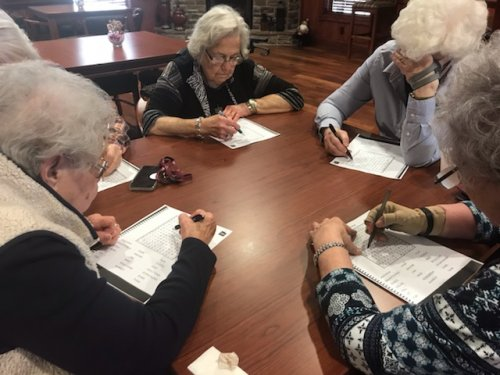 The ladies are concentrating hard on their crossword puzzles on Nationa Puzzle Day