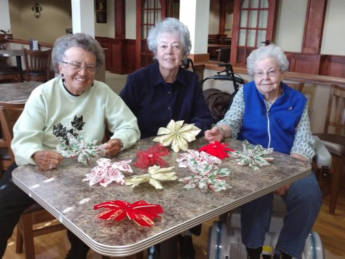 Mary, Sandy and Helen show off their Christmas decorations they made during arts & crafts