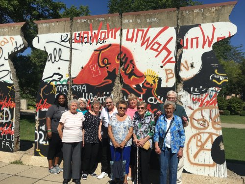 Residents are standing in front of a piece of the Berlin Wall at the Winston Churchill Memorial in Fulton, MO