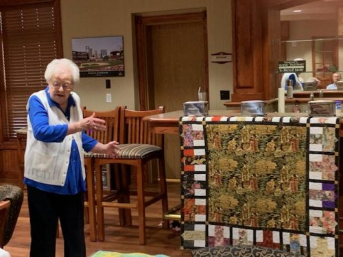 Helen is proud to show off one of the many quilts she has made at our show and tell activity.