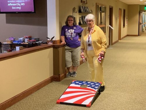 Carolyn, Asst. LEC, is cheering on Shirley as she tries to win the bean bag toss.