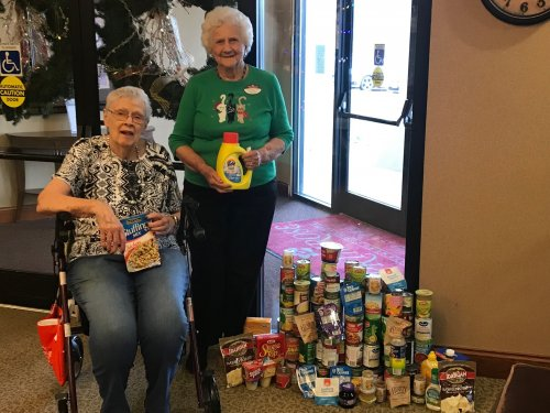 Carolyn and Dorothy showing off the can that the residents and employees donated to Harvesters here in KC!