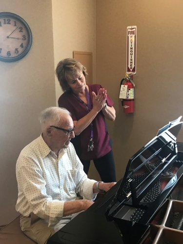 Nurse Cindy signing the 'St. Louie Woman' with John (our resident) on the baby grand!