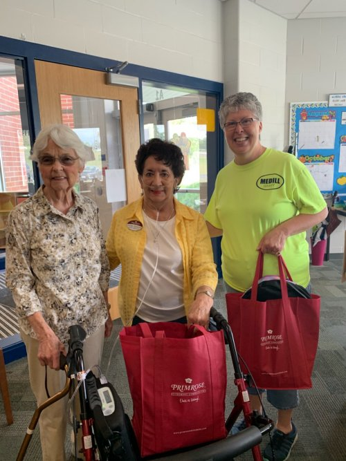 Two of the Helping Hands Committee presenting school supplies donations to a faculty member at Medill Elementary.