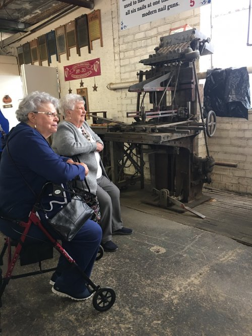 Mary and June are watching a washboard demonstration during our tour of the Columbus Washboard Factory.