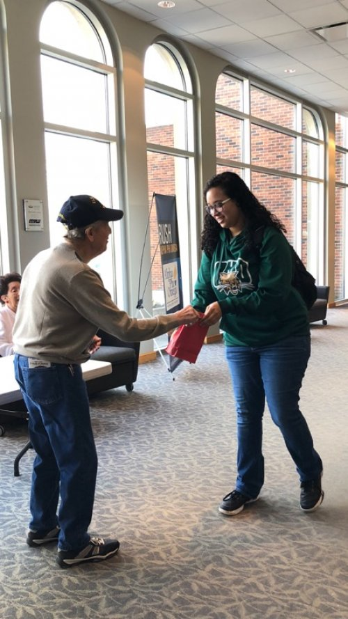 Don is handing a goody bag to one of the students at OUL during RAOK Day.