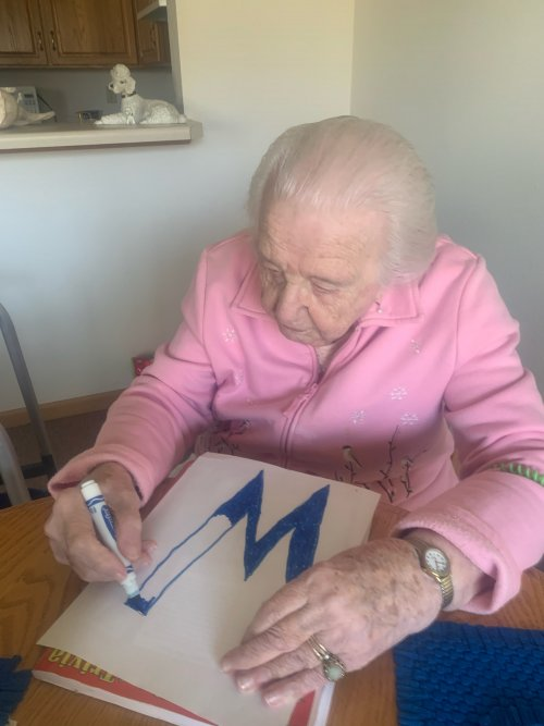 Dorothy is keeping busy by helping make a sign.