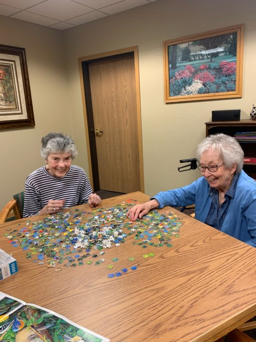 Neighbors having some laughs while working on a puzzle.