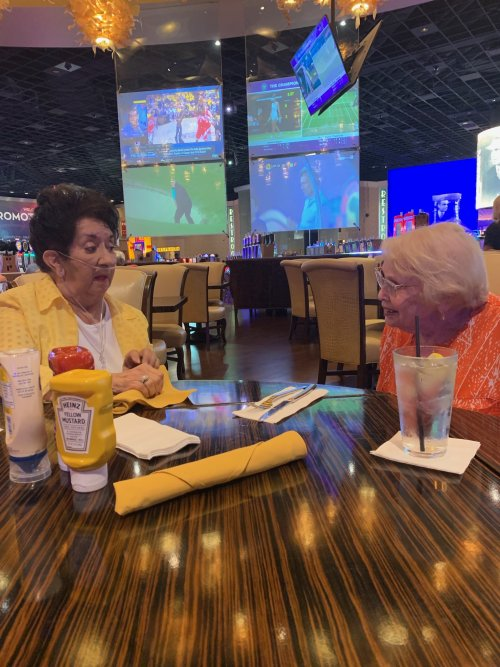 Cecillia and Pat are discussing their winnings so far, while waiting on lunch to arrive.