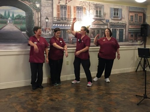 Tammy, Melanie, Eileen and Rose are doing the Hokey Pokey for the residents.