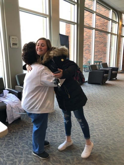 Cecilia receiving a hug from a student that just received  a gift card.
