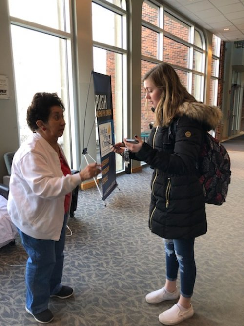 Cecilia handing one of the students a gift card during RAOK Day at OUL.