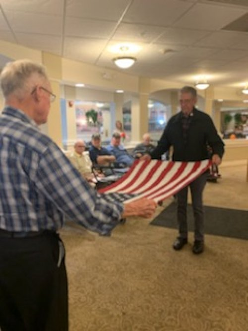 Dean and Herbert are folding the flag during The Veteran's Day Ceremony.