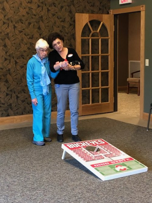 Vicki is trying to give Norma some pointers in Cornhole.