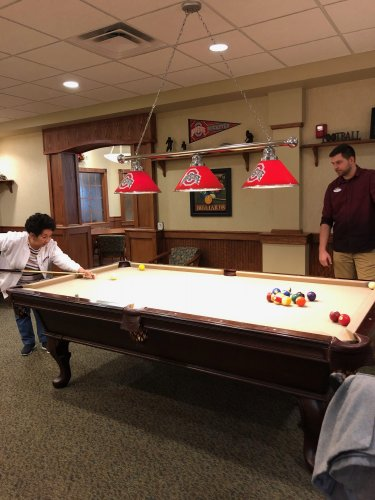 Cecilia is working on beating Brandon at a friendly game of pool.