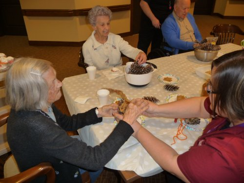 Molly and the residents create peanut butter birdseed feeders for our feathered friends