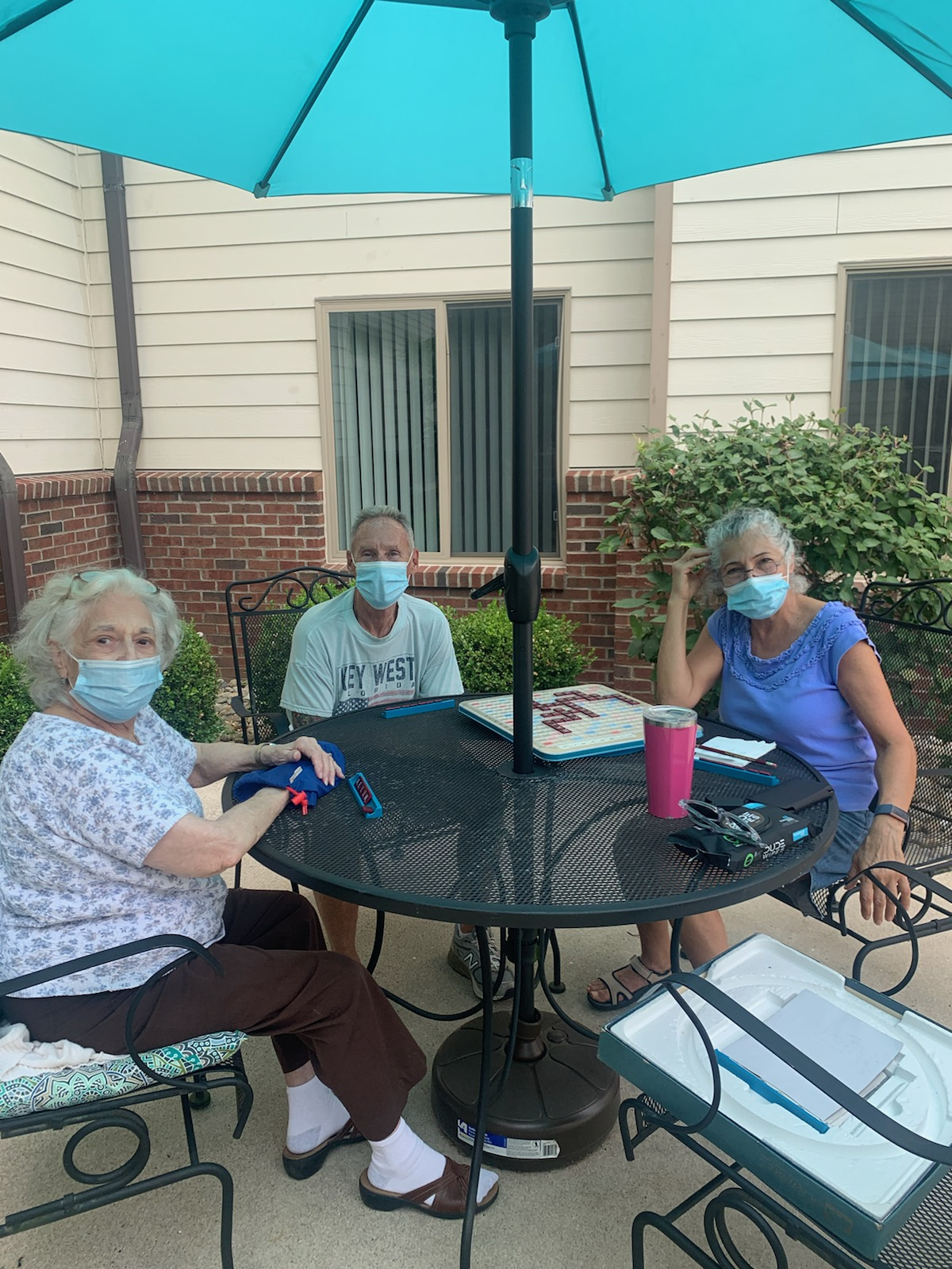 Emma and her family are enjoying the great weather by playing a game of Scrabble on the patio.
