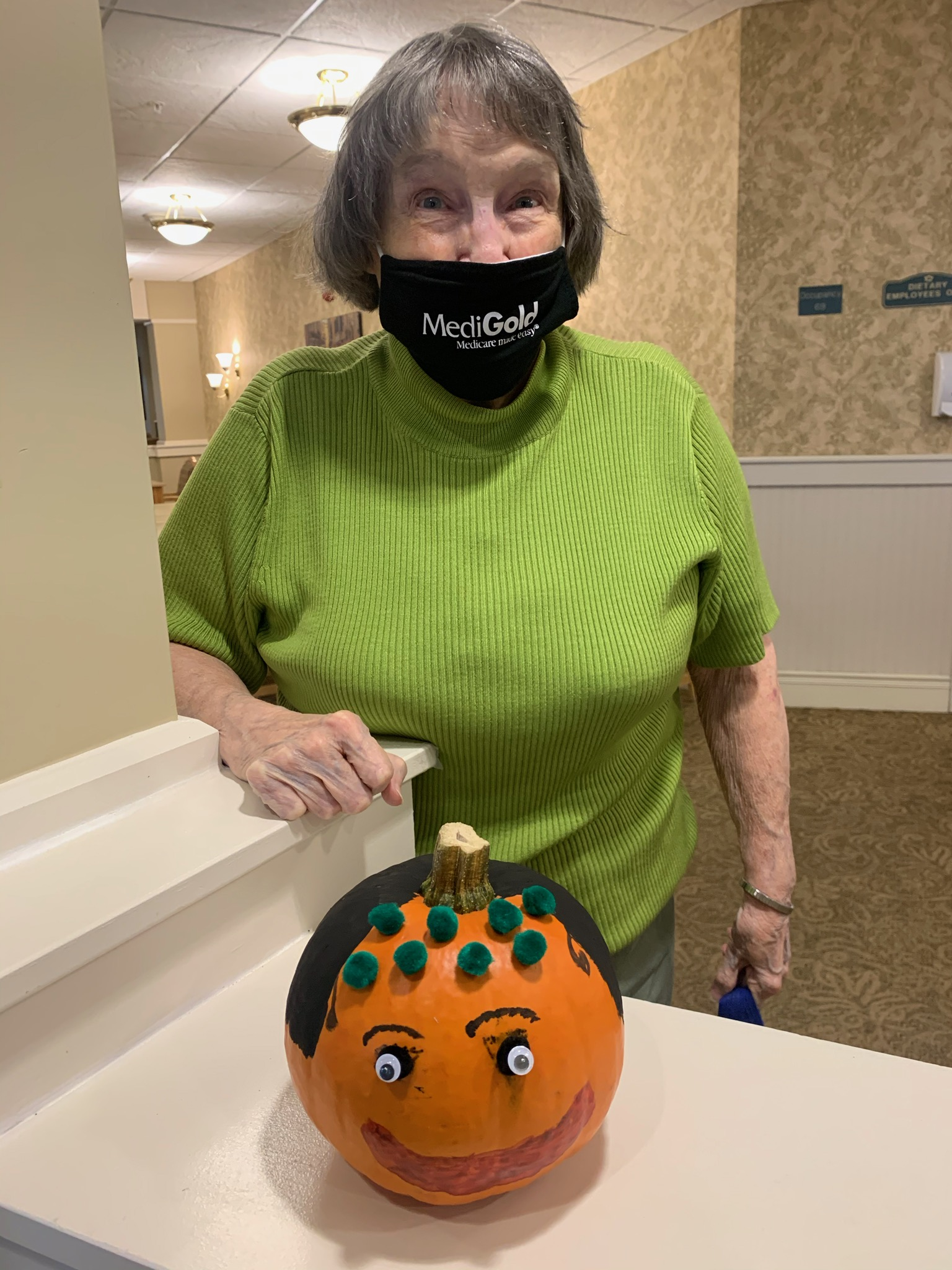 Thelma stands proudly by her pumpkin after winning first place in the pumpkin decorating contest.