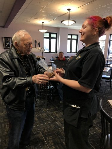 Jim is handing a treat bag and a Amazon gift card to one of the Culinary Students at Apollo.