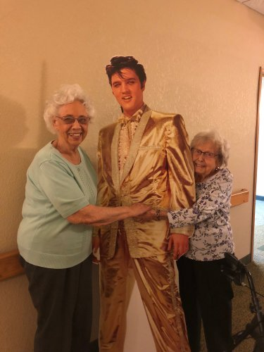 Geneva and Mildred are hugging Elvis because they were so excited they won the chance at Bingo for him to come to their apartments.