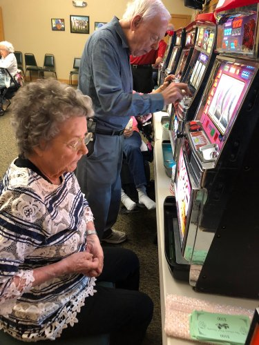 Eileen and Jim are trying their luck at the slot machines on the Pot-O-Gold Night at primrose of Lima.