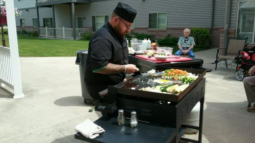 Employee Wes demonstrating how to cook on a hibachi grill.
