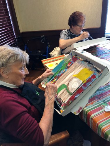 Jean and Joan painting a picture with Awakening Minds Art.