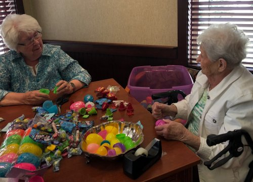 Anne and Marilyn are having a good time filling eggs for the Easter Egg Hunt!