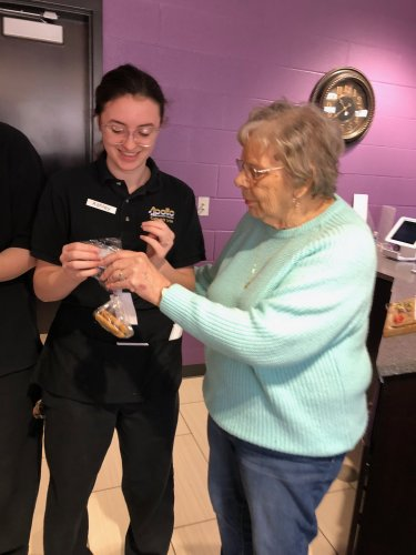 Betty is handing a treat bag and gift card to a student at Apollo.