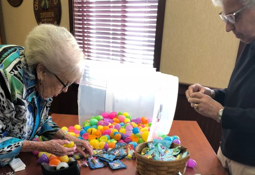 Jean And Alberta are putting the candy in the plastic eggs and snapping them shut.