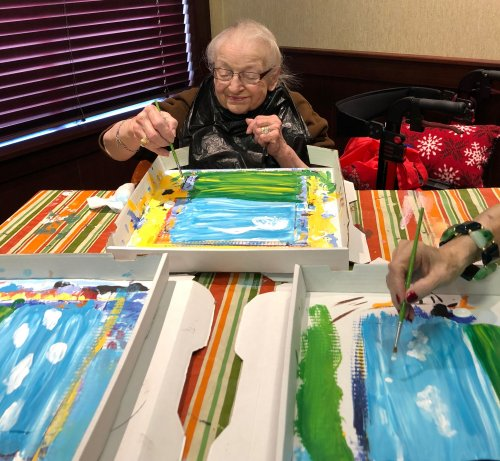 Betty enjoys painting a picture of mountains, sky, grass, and poppy flowers