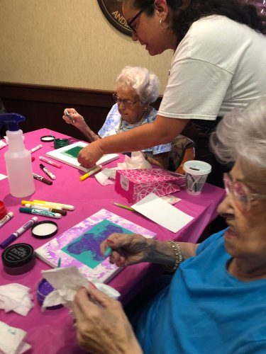Nurse Tonya is showing the residents how to do chalk stenciling.