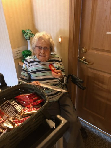 Mildred enjoys a candy bar and trivia while listening to Linell play the piano.