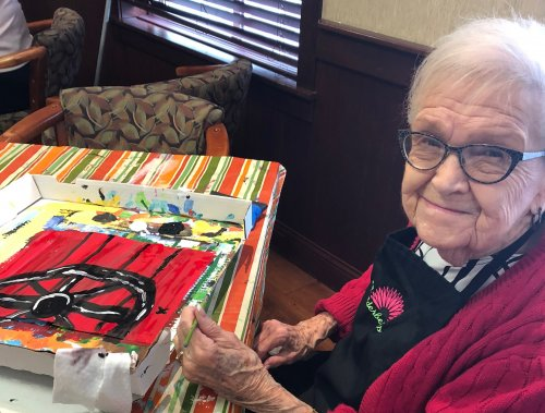 Jean W. is enjoying painting with the Awakening Minds class.