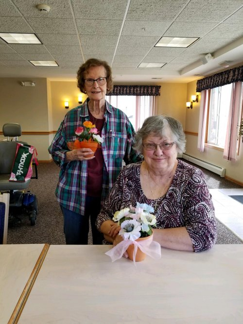 Jean and LeAnn show off their 'pretty pots' after an engaging craft experience.